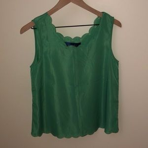 Sleeveless blouse with scalloped trim detail.
